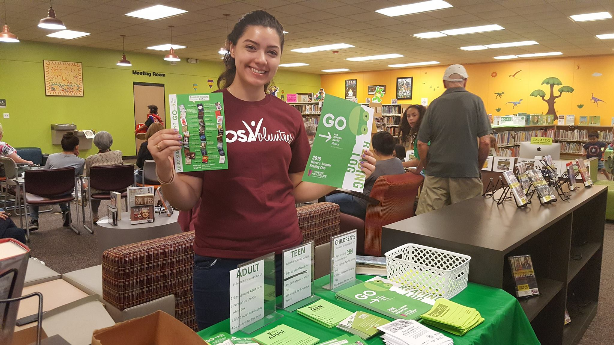 volunteer putting together summer reading green packets