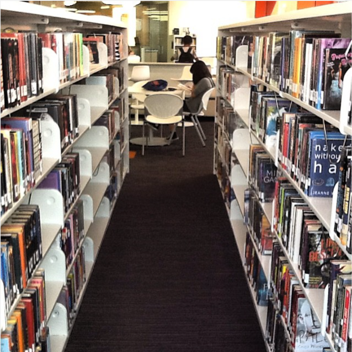 Teens reading at table and browsing the shelves through bookstacks.